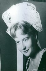 Portrait of a woman wearing something on her head looking towards the camera smiling.