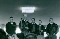 Men standing on the stage, smiling and giving speech.