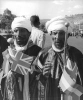 Two old men holding a United Kingdom flag during Queen Elizabeth's visit in Ethiopia.