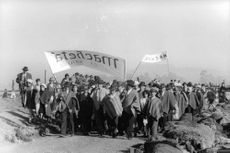 """People in procession, holding banners that say """"Macheta"""" or model."""