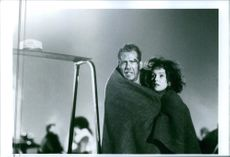 """Bruce Willis and Bonnie Bedelia standing together in one blanket in the scene from the movie, """"Die Hard 2""""."""