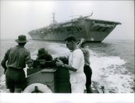 People in a boat, looking at the ship coming from opposite side.