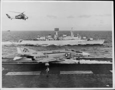 A helicopter flies over a ship and a carrier ship with a fighter plane