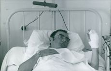Male patient lying on bed in hospital.