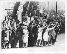 People standing on the side of the street, waving to their prince and princess.