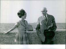 François Charles Mauriac and a woman standing in front of the breakwater wall. 1962.