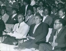 A group of well dress persons are sitting together.
