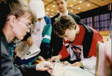 Swiss tennis player Martina Hingis writes autographs.