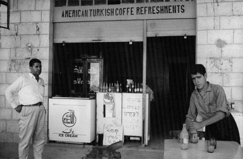 Men outside of a American Turkish Coffee Refreshments store in Israel.