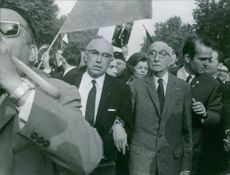 French novelist François Mauriac have standing with a group of people in Paris.