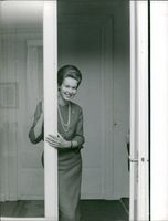 Princess Maria Gabriella of Savoy striking a pose, standing, leaning on the glass door, November 1960.