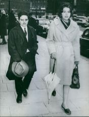 Man holding hat and woman walking on the road, holding umbrella and bag.  1960