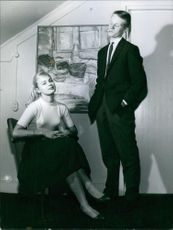 A man standing taking cigarette and woman sitting on a chair in a room.