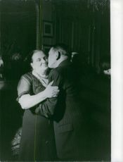 Rene Coty kissing a woman.
