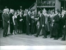 Frank Sinatra about to shake hands with Nina Petrovna Khrushcheva. People around them.