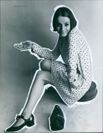 Year ?  A photo of woman siting and gesturing looking towards the camera.