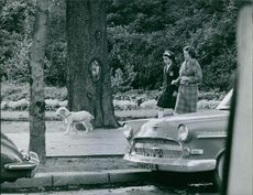 Lady Sarah Consuelo Spencer-Churchill walking on side walk with a girl while talking to her, 1961.