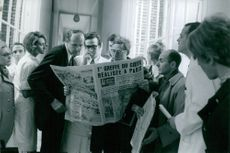 People gathered together reading a news paper, 1968.
