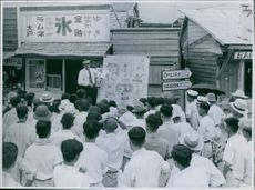 A Japanese crowd listening to a man speaking in front of them, discussing a topic related to war.