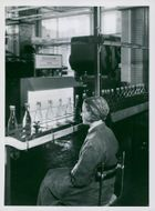 Pharmacy's new factory. One of the workers' checks examines the filled bottles against light