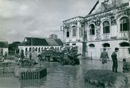 Picture of people and an army truck in the flooded street of Vietnam.