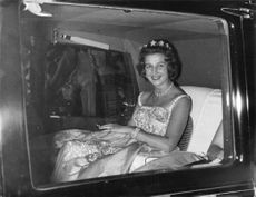 Princess Alexandra, inside the car, looking through the window, smiling.