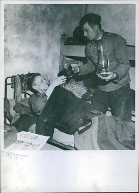 Soldier giving a mug of water to the man in Poland, 1947.