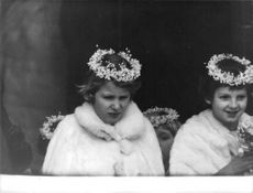 Princess Anne sitting with another girl, flowers in their hair.