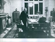 French conservative politician and former Prime Minister Antoine Pinay standing in the office.