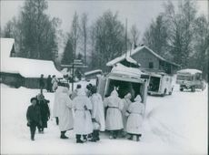 A group of men gathered outside a vehicle parked in an are covered with snow during the war, 1940.