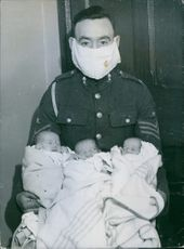 Sergeant E.J. Sinclair wearing a mask while holding his triplets. 1939.