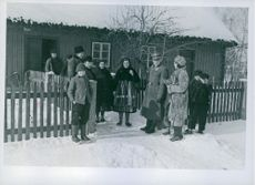 Soldier standing with family, outside the house. Poland 1940