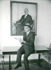 Konrad Hermann Joseph Adenauer sitting on table.