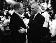 Yul Brynner shaking hand with man.