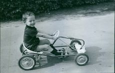 A child sitting and driving the toy car, looking away and eye closed.