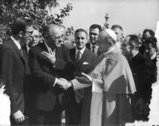 Pope Paul VI shaking hands with a man.