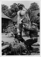 A scene from a film featuring two men raising an effigy.