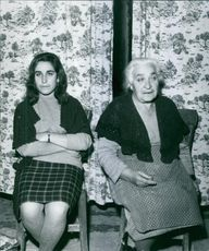 An old woman sitting with young woman on chairs.