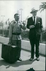 Trevor Howard standing with a man carrying a luggage, 1960.
