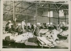 A nurse checking on the patients in a hospital ward during the war in Germany, 1915.