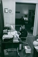 James Meredith sitting and working on his desk, 1966.