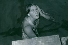 A photo of a woman bathing in a pool and looking up, 1969