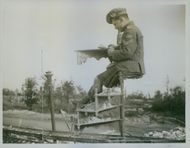 Soldier siting while looking at something during Tyskland war.