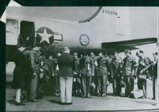 Standing beside an aircraft, wounded American servicemen pray after hearing of Germany's surrender, 1945.