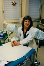 Dr. Agneta Bergquist  sitting  at the end of the examining bed in her hospital clinic.