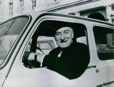 Pierre Marcilhacy driving car, looking towards the camera and smiling.
