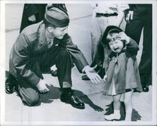 A cute little girl crying, soldier smiling while looking at her.