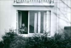 A man standing on the balcony, holding gun.