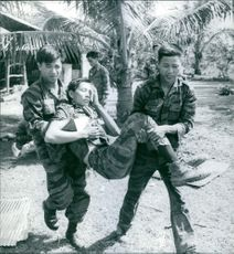 Soldiers lifted and taking away the wounded soldier.