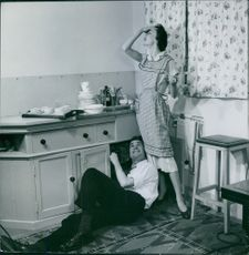 Man and woman doing funny activity in the kitchen. 1954